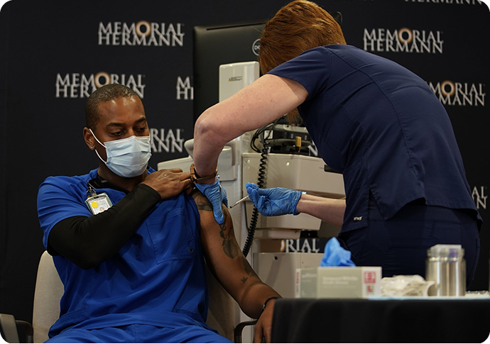 photo of Robert Luckey, RN, receiving first COVID-19 vaccine administered at Memorial Hermann, Dec. 15
