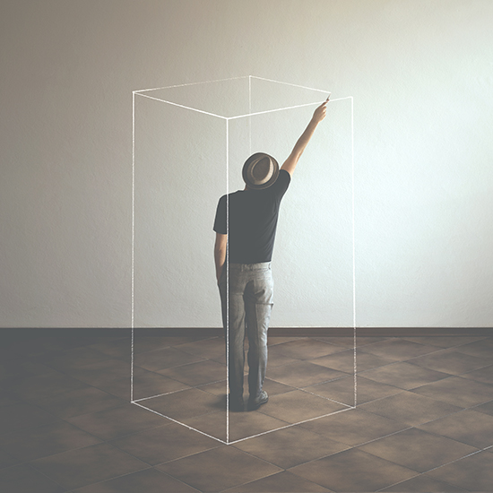 person standing in an open room drawing imaginary walls around them