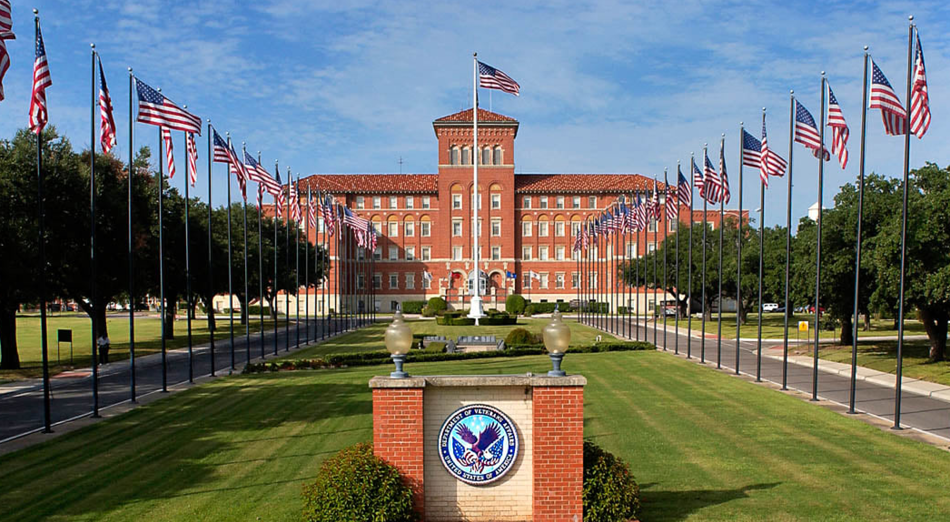 photo of the Central Texas Veterans Health Care System campus, with the building in the distance across a field of flag poles flying the American flag