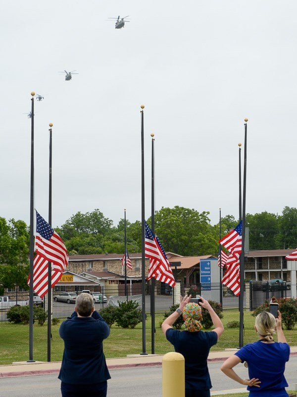 staff at the Central Texas Veterans Health Care System standing near flags at half mast as helicopters approach