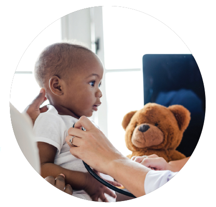 photo of a child receiving medical attention, a teddy bear looks on