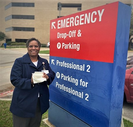 photo of hospital chaplain standing next to parking lot sign