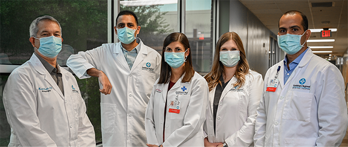 photo of a medical team standing together for a group photo, each wearing a white lab coat and a blue mask