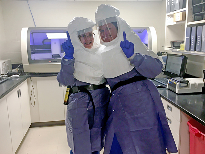 photo of a two medical lab technicians in protective gear