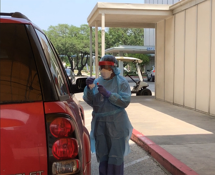 photo of a medical staff checking a testing vial while standing next to a vehicle