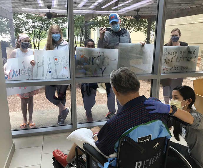 photo of a family holding signs of birthday greetings outside a windowed patio inside which a COVID-19 patient in a wheelchair is attended by medical staff