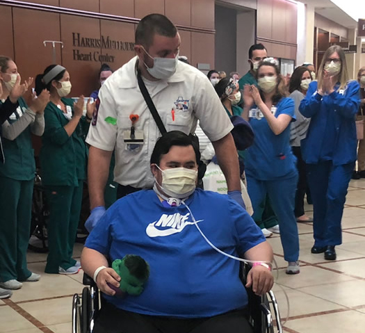 photo of a COVID-19 patient in a wheelchair with the hospital medical staff cheering behind him