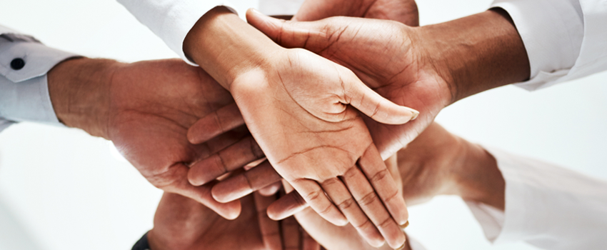 photo of multiple people pressing hands together in a team fashion