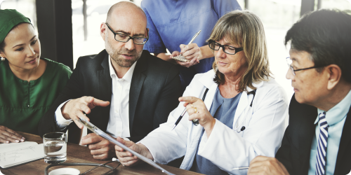 image of a doctor meeting with board members